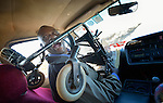 Dominik Tengani sits in the front passenger seat of a kombi near his home in Kuwadzana, Zimbabwe. Tengani is vice chair of the Spinal Injuries Association of Zimbabwe, which supports and advocates for the rights of people living with spinal injuries. He says doctors have been unable to diagnose the cause of his medical condition. He uses an appropriately-designed and fitted wheelchair provided by the Jairos Jiri Association with support from CBM-US. Kombi drivers often refuse to allow people in wheelchairs to ride, or charge them extra for taking their wheelchair along. In Tengani's case, his wheelchair disassembles, yet he is forced to ride with the main frame of the chair over his shoulders.