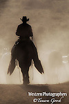 A cowboy pushing horses in the dust.