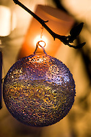 Close up of a glass bauble with a purple and gold finish