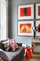 A red retro table matches the colour of the artwork in this living room