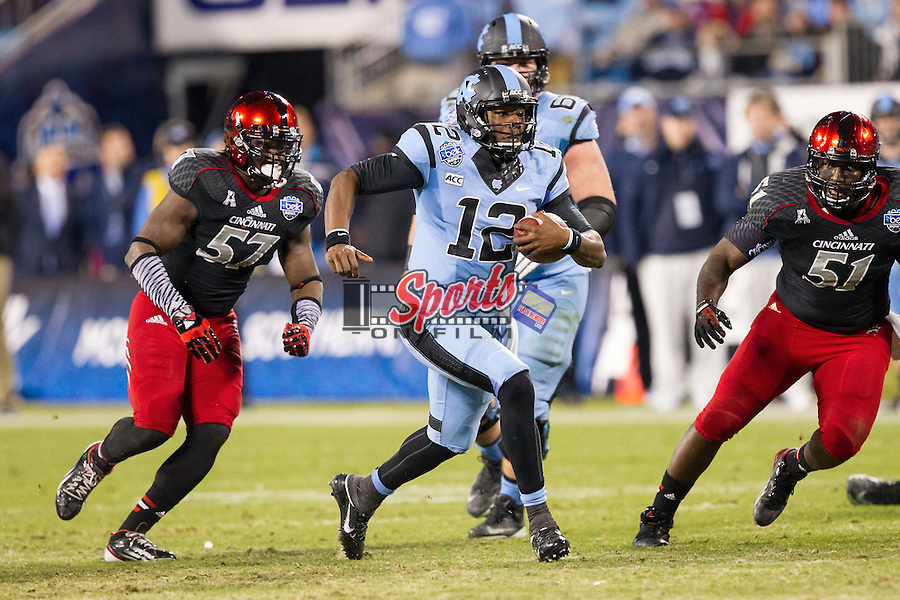 Marquise Williams (12) of the North Carolina Tar Heels runs away from the pursuit of Greg Blair (51) and Clemente Casseus (57) of the Cincinnati Bearcats in the Belk Bowl at Bank of America Stadium on December 28, 2013 in Charlotte, North Carolina.  The Tar Heels defeated the Bearcats 39-17.   (Brian Westerholt/Sports On Film)
