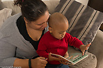 18 month old toddler boy with mother, read to, pointing at llustration in book