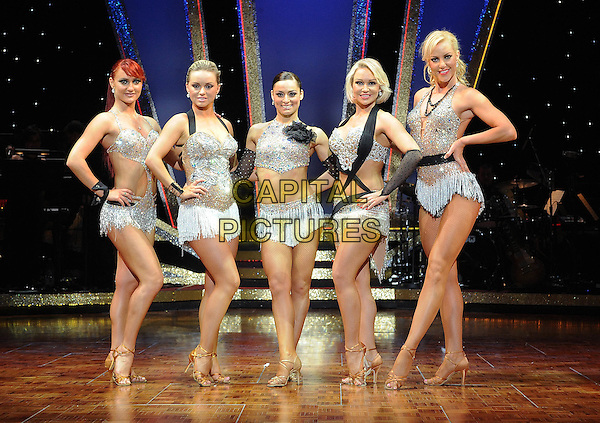 DANCERS - Aliona Vilani, Orla Jordan, Favia Cacace, Kristina Rihanoff and Natalie Lowe.Strictly Come Dancing - The Professionals Tour, featuring 10 popular dancers from the hit BBC1 series, The Brighton Centre, Brighton, East Sussex, England, UK, 29th April 2010.full length show concert on stage black  silver sparkly costume outfit bra top dress fishnet tights arm warmer beaded flower corsage hand on hip gold strappy shoes sandals jewel encrusted crystals tassels fringed .CAP/BEL.©Tom Belcher/Capital Pictures.