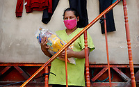 SOACHA, COLOMBIA - APRIL 15: A woman carries a bag after the local government workers deliver food to the community during the mandatory preventive quarantine to prevent the spread of the new coronavirus in Soacha Colombia on April 15, 2020. Soacha's mayor visited the slums of the town handing out baskets of food to help families in difficult financial times due to Covid-19 pandemic. (Photo by Leonardo Munoz/VIEWpress via Getty Images)