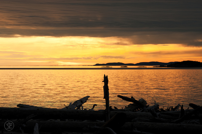 Sunset over the driftwood piled on the shores of Lake Superior, Pukaskwa National Park.