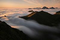 Mountain peaks rise above sea of summer fog, Flakstadøy, Lofoten Islands, Norway