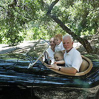 Malcolm McDowell with his wife Kelley and their sons Beckett and Finn in his vintage Jaguar