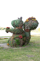 Squirrel statue that holds flower at the city park. Rawa Mazowiecka Central Poland