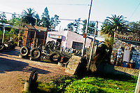 A typical street shop in Juanico advertising its services to re-vulcanize tyres - Gomeria - displaying tyres of different shapes and forms from cars, tractors and bicycles. Uruguay, South America
