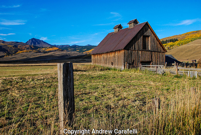 Late afternoon sun illuminates an old barn and changing aspens  on Cold Spring Ranch near Crested Butte, Colorado.