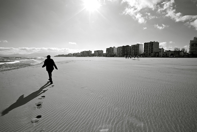 A woman walks on the beach in Perpignan, France. Feb. 14, 2009.