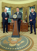 Washington, D.C. - May 8, 2006 -- United States President George W. Bush names Air Force General Michael Hayden (R) to be the next Central Intelligence Agency (CIA) Director, as National Intelligence Director John Negroponte looks on, in the Oval Office of the White House on May 8, 2006. Hayden will replace Porter Goss if confirmed. <br /> Credit: Roger Wollenberg - Pool via CNP
