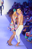 Couple dances at Luli Fama Swimwear Show during Mercedes Benz IMG Fashion Swim Week 2014 at The Raleigh Hotel, Miami Beach, FL on July 21, 2013