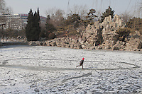A Chinese boy runs on a frozen pond at the Ritan Park in Beijing, China, February 9, 2013.