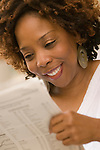 African American woman reading newspaper, smiling