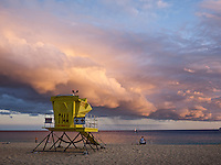 A lifeguard shack on Makena beach facing a fisherman, sailboat and big peach colored sunset clouds on Maui.