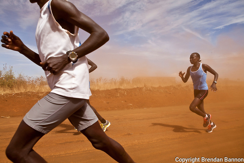 Florence Kiplagat, one of Kenya's leading women marathon runners, works her way through a squall of dust kicked up by a farmer's tractor near Eldoret, Kenya.