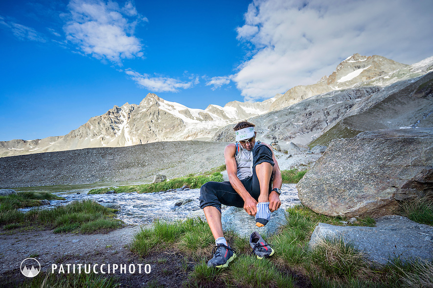 Ueli Steck putting his shoes on after a creek crossing. He is descending to Zermatt after peak 41 of his 82 Summit project. The Zinalrothorn above Zermatt marked the halfway point of his goal of all 82 4000 meter peaks done entirely under his own power.