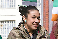 St Patricks Day parade High Street Digbeth.Girl with green earring High St Custard Factory to her back