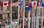 The march passes behind a row fo Canadian and Provincial flags flying near city hall in Toronto. Around 1500 people came out in Toronto today to take part in the Defend our Climate rally. The rally was a part of a national day of action drawing attention to pipelines, tar sands, climate change and other resource extraction that is exacerbating climate change, affecting First Nations and leading Canada towards a Petrostate.