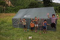 Nepal, Gorkha District, Arughat, Gorkha. Nepal Youth Foundation. Destruction after the earthquake. Children where NYF is setting up their donated tents for displaced people.