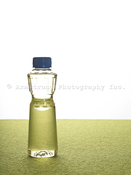 Soybean oil in a plastic bottle with no label, blue cap, green background.