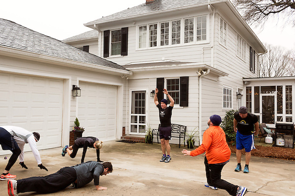 December 22, 2014. Lexington, North Carolina.<br /> Mayor Newell Clark, center, and the other members of his workout group perform a variation of the burpee in his driveway to end their exercise routine.<br />   Newell Clark, the 43 year old mayor of Lexington, NC, leads a group of friends and colleagues on a 4 times a week exercise routine around downtown. The group uses existing infrastructure, such as an abandoned furniture factory, loading docks, stairs, and handrails to get fit and increase awareness of healthy lifestyles in a town more known for BBQ.<br /> Jeremy M. Lange for the Wall Street Journal<br /> Workout_Clark