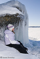 Girl sitting near ice caves on Lake Superior in winter
