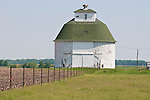 White painted masonry round corn crib and barn, green roof, fence line, rural Ill.