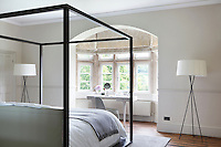 A simply furnished but elegant bedroom, lit by a stone bay window
