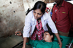 younge bangladeshi doctor helping a woman after she got out of a surgery onboard of the Rongdhonu Friendship Hospital docked outside the mongla port 29 April 2014