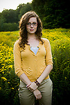 Young woman wearing eyeglasses standing in open meadow looking at camera