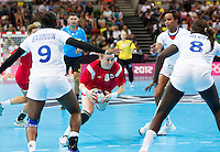 28 JUL 2012 - LONDON, GBR - Karoline Dyhre Breivang (NOR) of Norway (centre, in red) looks for a way through the French defence during the women's London 2012 Olympic Games Preliminary round handball match at The Copper Box in the Olympic Park, in Stratford, London, Great Britain (PHOTO (C) 2012 NIGEL FARROW)