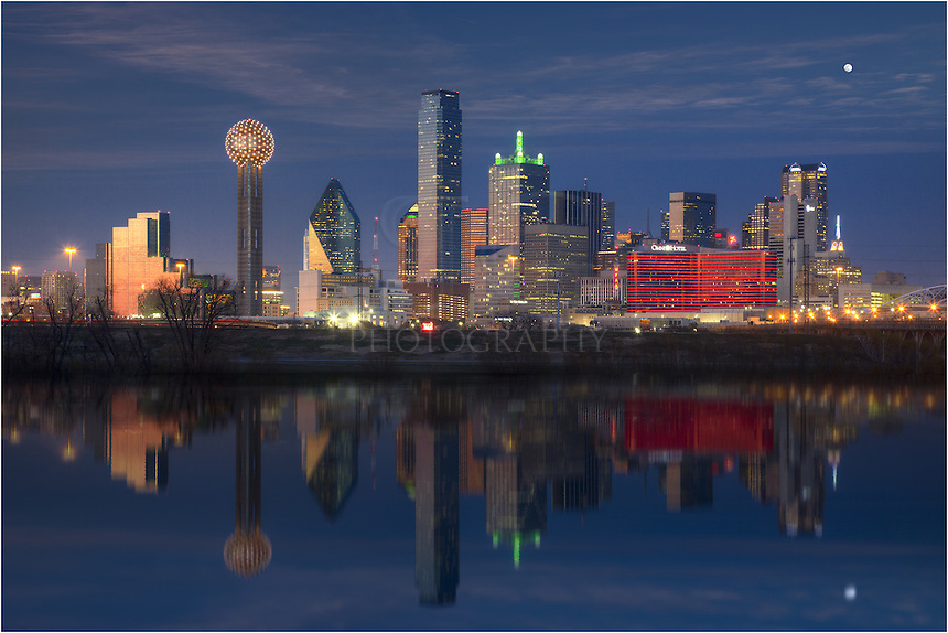 From the banks of the Trinity River, the Dallas skyline is reflected in the still waters of a calm Autumn evening. The waters were high after a lot of rain.