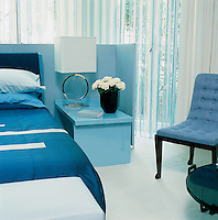 A master bedroom with a pale blue leather screen, lacquer table, leather and silver disc light and silk applique bedspread all by David Collins. The 1940s chair is by Marc du Plantier.