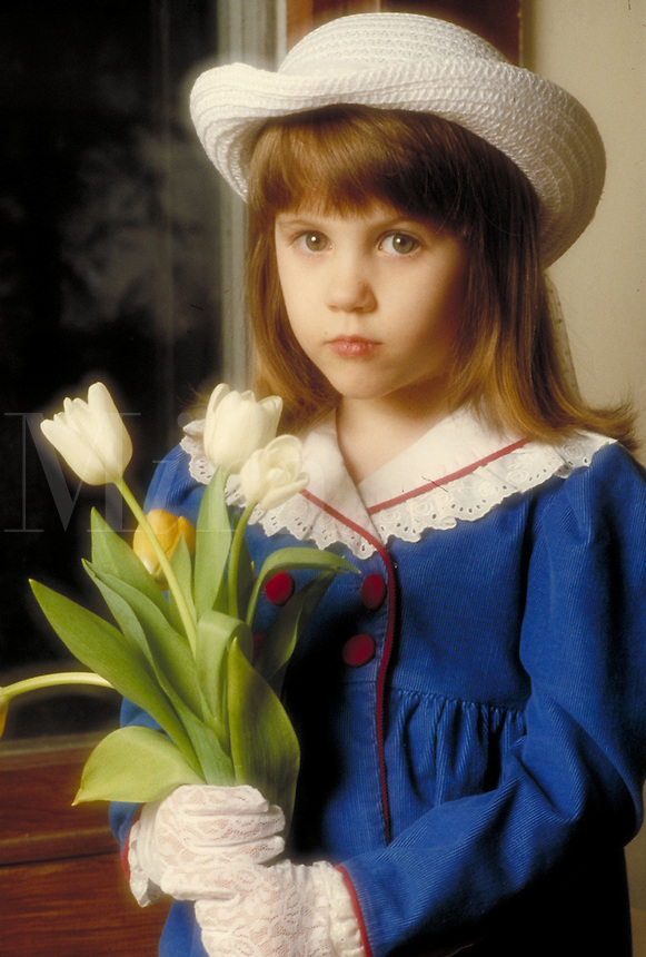 Small girl in hat with flowers wearing blue dress. Family. Douglaston NY.