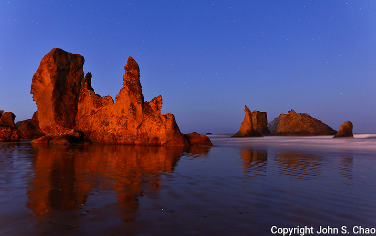 Bandon, Oregon sea stacks under stars, reflected in wet sand at low tide on Bandon Beach at dawn.