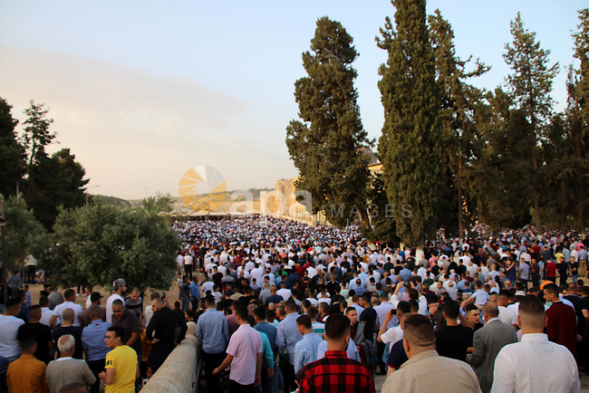 Palestinian Muslims perform the morning Eid al-Fitr prayer near the Dome of Rock at the Al-Aqsa Mosque compound, Islam's third most holy site, in the old city of Jerusalem on June 5, 2019. Muslims worldwide celebrate Eid al-Fitr marking the end of the fasting month of Ramadan. Photo by Abdalrahman Alami