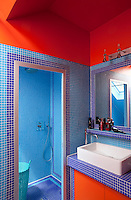 The red and blue bathroom has walk-in-shower tiled in turquoise and indigo blue mosaic tiles that extend round the walls of the bathroom