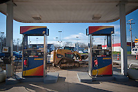 Gasoline pumps are repaired at a station closed while road construction interrupted business. The store is readying itself for reopening as the phase of road construction in front of its entrances is completed.