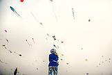 USA, Washington State, Long Beach Peninsula, International Kite Festival, a woman flies her kite during the flat and bowed kite mass ascension