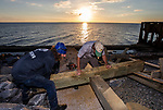 PORT SAINT JOE, FL - OCTOBER 14: Ryan Tyson, left, and Jevron, with Tropical Tree Care, out of Ft. Lauderdale, reported to Port Saint Joe for FEMA work and decided to build a large cross while waiting for their assignments at the Port St Joe Marina from salvaged eight inch thick wood that washed up during Hurricane Michael on October 14, 2018 in Port Saint Joe, Florida. (Photo by Mark Wallheiser/Getty Images)