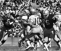 Seahawk QB Jim Zorn about to be sacked by Raider Howie Long #75. Photo by Ron Riesterer