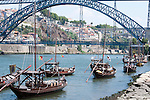 Boats used to transport wine barrels sit on the Douro River in Porto, Portugal with the Don Luis iron bridge in the background.