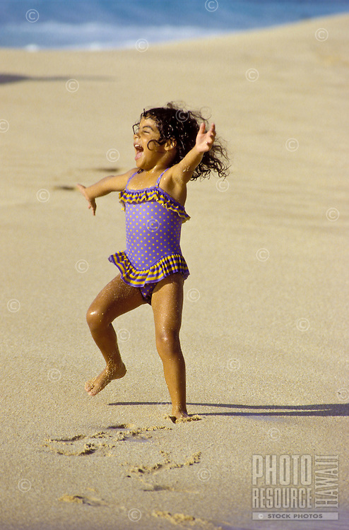 Young girl with arms spread wide laughs with joy while playing at beach on the north shore of Oahu.