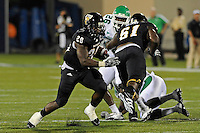 1 September 2011:  FIU running back Darriet Perry (28) carries the ball as North Texas Forlando Johnson (26) watches in the second half as the FIU Golden Panthers defeated the University of North Texas, 41-16, at University Park Stadium in Miami, Florida.