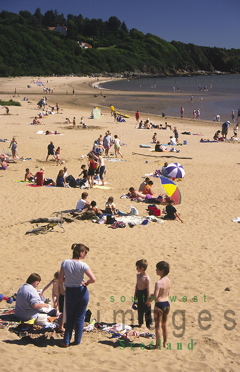 Families enjoy the summer sunshine on Sandyhills beach on the Solway Firth Scotland UK