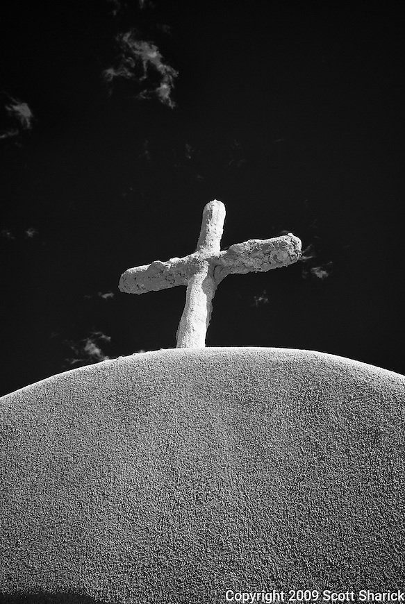 An infrared picture of a cross on top of an adobe mission in Mew Mexico.
