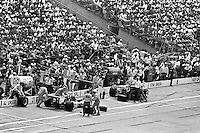 INDIANAPOLIS, IN - MAY 29: Al Unser #21 Parnelli VPJ6B 001/Cosworth TC and Mario Andretti #9 McLaren M24 3/Cosworth TC make pit stops during the Indianapolis 500 on May 29, 1977, at the Indianapolis Motor Speedway in Indianapolis, Indiana.
