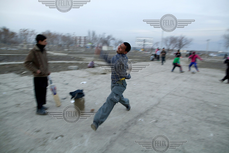 Boys play cricket (and football in the background) near the ruined Darul Aman Palace on the outskirts of Kabul.